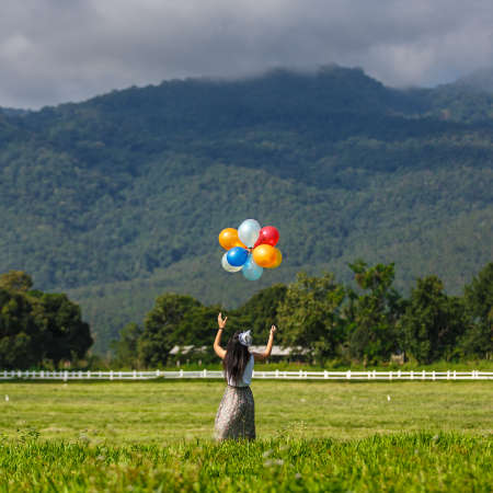A girl playing balloon in grass field with mountain background photo