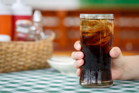 Hand holding glass of cola drink on table with restaurant background photo
