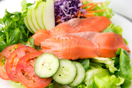 closeup vegetable salad top with smoked salmon and sliced green apple on a white plate Foto de archivo