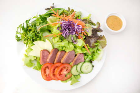 vegetable salad top with sliced roasted duck in white plate served with thousand island dressing in a dipping bowl on white background