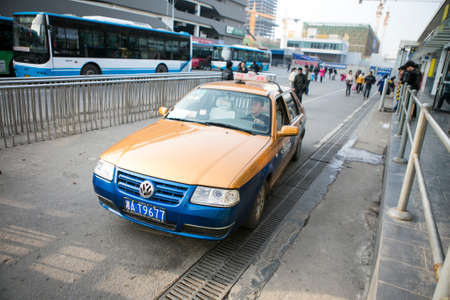 Changsha, China - Feb 20,2014 a yellow navy blue chinese taxi driving slowly on the road