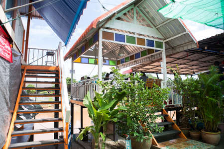 Ayutthaya, Thailand - 16 August 2020 : local asian colorful outdoor pavilion where is built beside a river connected to ladder decorated by a lot of small green trees in plant pots