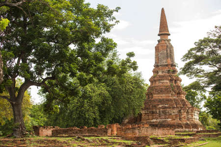 An old ancient traditional Thai bell inverted shape red bricks pagoda in outdoor peaceful green yard with and big trees Stock Photo