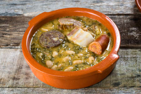 typical northern spain dish made with beans, cabbage and pork meat served in traditional clay pot.