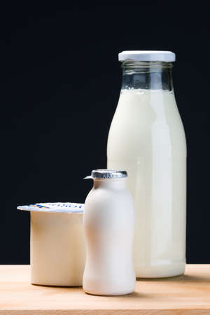 milk bottle, yogurt and probiotic drink yogurt in vertical composition.Black background photo