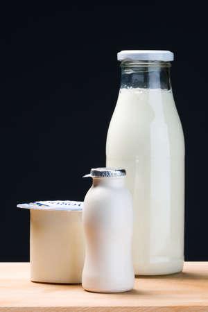 milk bottle, yogurt and probiotic drink yogurt in vertical composition.Black background Stock Photo