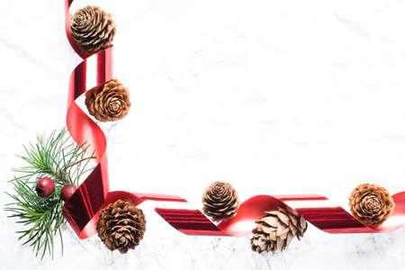 crata�gus: frontera estacional hecha de alerce con conos de pino, bayas, Crataegus y cinta roja sobre fondo blanco