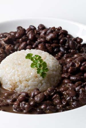 weißer Reis accompained durch schwarze trockene Bohnen in einer Platte mit Petersilie Dekoration serviert. vertikale Zusammensetzung