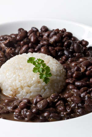 white rice accompained by black dry beans served in a plate with parsley decoration. vertical composition Stock Photo