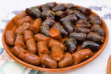 spanish tapas: variety of spanish pork sausages on clay plate