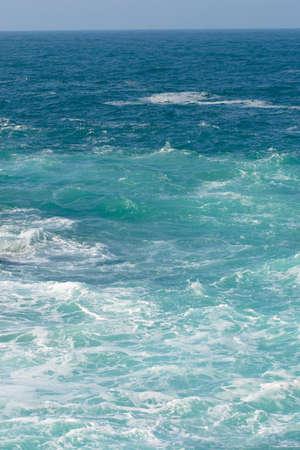 mare agitato: Cielo blu e mare con schiuma bianca nella composizione verticale