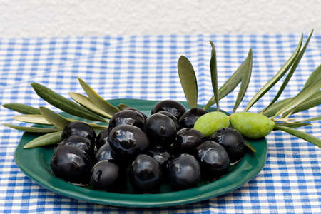 Black olives on a plate with olive leaves decoration