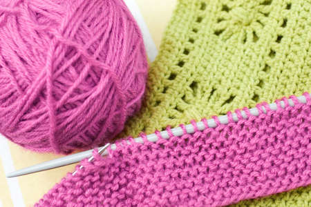 Knitting needls, yarn ball and pieces of knitted and crochetted works