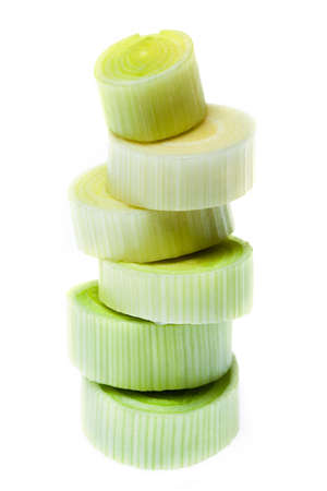 Some pieces of chopped leek stacked on white background