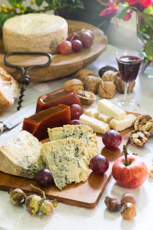 Rustic Still-life of Asturian blue cheese (cabrales) with sweet quince, nuts, hazelnuts, grapes, apple, and red wine