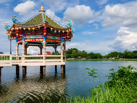 thani: Chinese Temple near the lake with green grass at the front