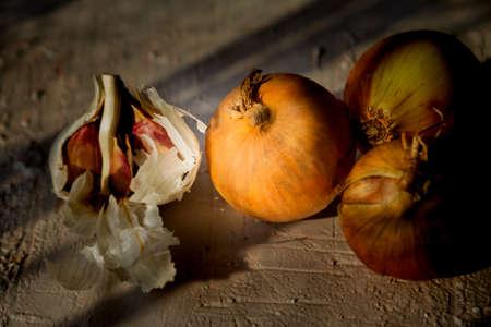 Three onions and garlic. Rough, bright background. Deep shadows. Natural light.