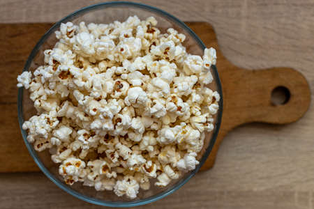 Popcorn in a glass bowl. Processed corn. Snack to the movie. In the cinema. Before the movie.