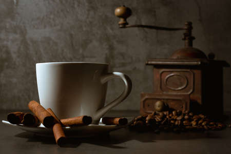 White cup, cinnamon and coffee beans on a gray background. Morning coffee. Coffee shop menu.