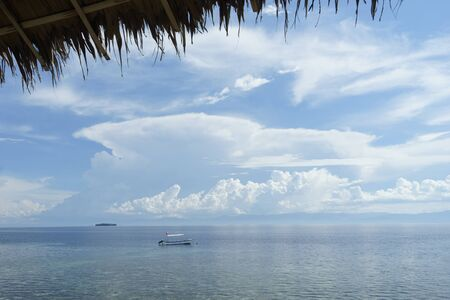 philippine: Diving boat with philippine flag on the surface of tropical sea under blue sky with many beautiful clouds
