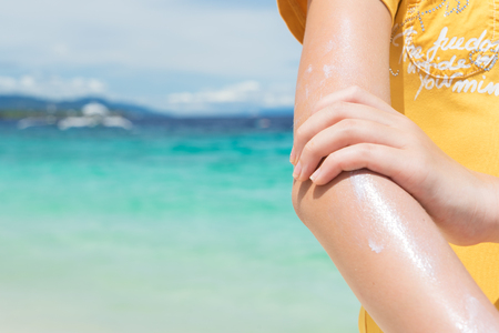 junges Mädchen appleng Sonnenschutzcreme auf ihrer Hand auf dem Strand nah an tropischem Türkismeer unter blauem Himmel am sonnigen Tag