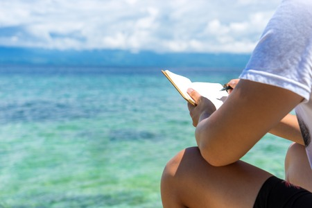 caucasian man is sitting on the coast of tropical turquoise sea and wrigting by pen in note pad at sunny summer day under cloudy sky