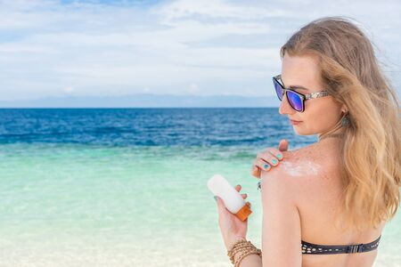 suncare: young woman applyng sun protector cream on her hand on the beach close to tropical turquoise sea under blue sky at sunny day Stock Photo