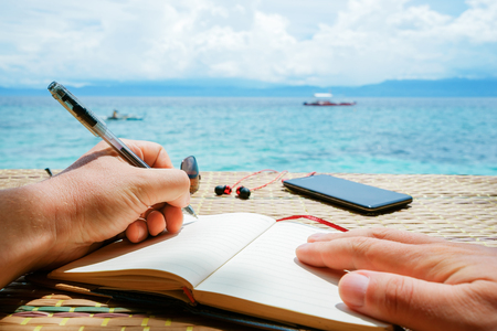 caucasian man is writing sime idea, message or letter in his notepad by pen in left hand while he sitting on the beach of tropical sea with boat