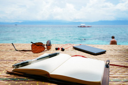 Opened empty notepad is on the table with sunglasses, phone and headphones at the tropical sea background and philippine boat on his surface. At sunny day under cloudy sky Stock Photo