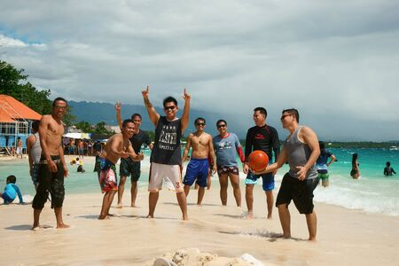 philippine: Moalboal. Cebu. Philippines - 06 aug 2016: Big company of philippine friends with basketboll is getting fun on the tropical beach close to turquoise wavy sea under stormy sky at gray day