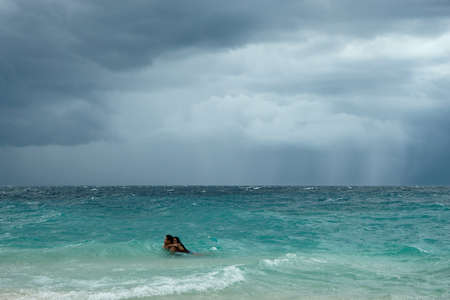 Moalboal. Cebu. Philippines - 06 aug 2016: Philippine young couple swimming in stormy tropical sea under cloudy dramatic sky of coming storm between big waves at gray day