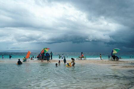 Moalboal. Cebu. Philippines - 06 aug 2016: Philippine families getting fun and rest while storm is coming to the tropical beach, from wavy sea under cloudy grey sky