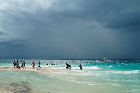 Moalboal. Cebu. Philippines - 06 aug 2016: Philippine families getting fun and rest while storm is coming to the tropical beach, from wavy sea at gray day