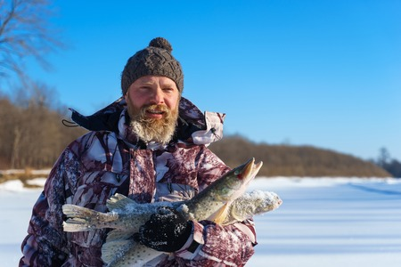 Bearded man is holding frozen fish after successful winter fishing at cold sunny day