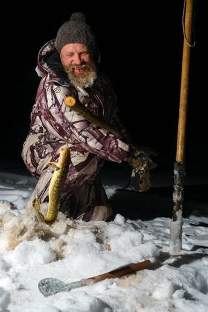Bearded man is holding fish and smiling at dark winter night