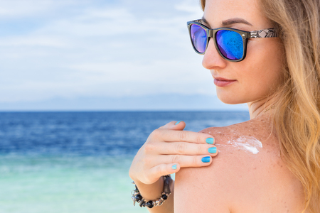 suncare: young woman with sunglasses applyng sun protector cream at her hand on the beach close to tropical turquoise sea under blue sky