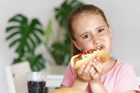provocative woman: Young cute european girl in t-shirt is eating unhealthy food like hot dog and chips at sunny day
