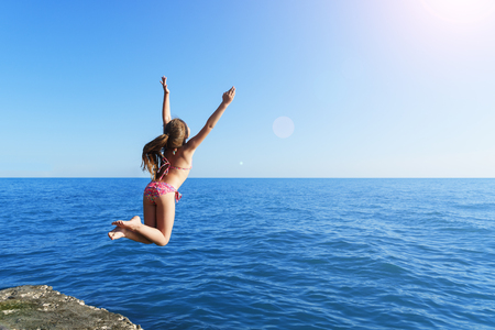 young european cute girl is jumping and flying to the calm blue sea from concrete breakwater towards summer soft sun under clear sky