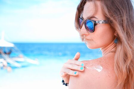young woman applyng sun protector cream on her hand on the beach close to tropical turquoise sea under blue sky at sunny day Stock Photo