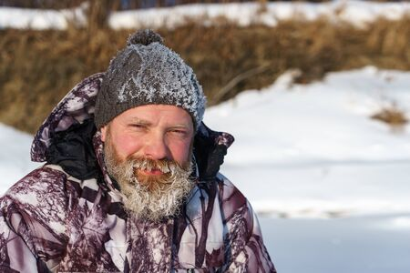 One euriopean bearded fisher man or hunter with ice and hoarfrost on beard is looking to the camera with smile at day time