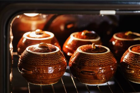 Six hot brown clay ceramic pot with backed or stewed food inside oven under lamp
