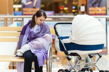 紫のストールで若い欧州女性が彼女の小さな子供が一日の時間で公共の場所のショッピング モールで白いベビーカーに近い授乳 写真素材