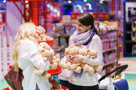 two women like gay couple or friends with white baby carriage is playing with toys and getting fun by toy bear in the big colorful supermarket.