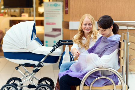 Young european gay couple or friends women with infant is sitting on bench close to white baby carriage while one of them breastfeeding son at public place shopping mall at day time. Stock Photo