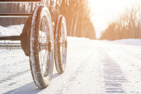 baby carriage with inflatable wheels on the winter snow road in some forest under bright sun at light day, toned