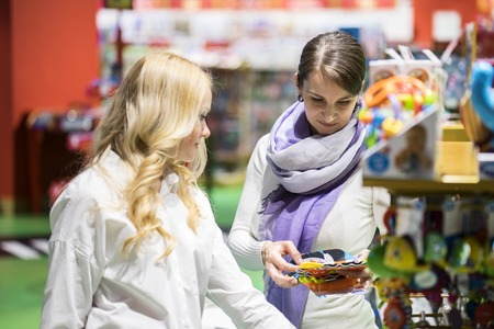 two women like gay couple or friends choose toy and getting fun in the big colorful supermarket at day time