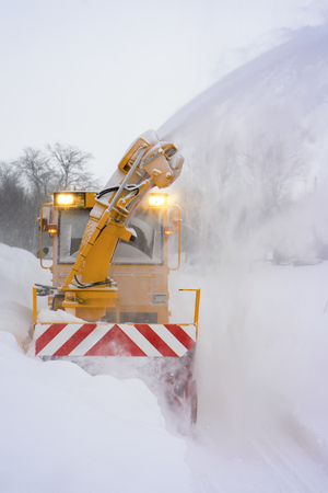 Big yellow snowplough with screw and helix is cleaning the road while a powerful stream of white snow go out of it at day time Stock Photo