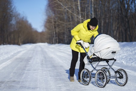Caucasian mom in yellow coat and sleeves is walking with white baby carriage on snow road among the forest at winter sunny day
