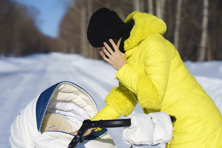 Caucasian mom in yellow coat is walking with white baby carriage on snow road among the forest and talking by phone at winter sunny day Stock Photo