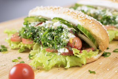 fast junk food delicious hot dog with juicy greenery and bbq sausage on the table close to small Cherry tomato Stock Photo - 103263153